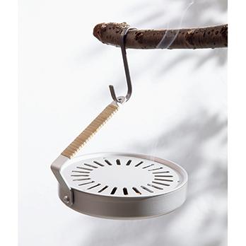 庭先の枝や、テラスの物干しなどに吊るして使うこともできる。天然の除虫菊を主成分とする蚊取り線香(直径12cm、30巻)が付属。