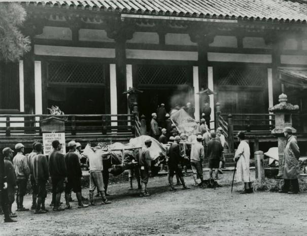 「疎開先から戻る東大寺法華堂四天王像」。白い布に包まれた仏像が堂内に運び込まれるところ(撮影1945年11月 *)。写真提供/入江泰吉記念奈良市写真美術館(*印は展覧会の展示作品)。