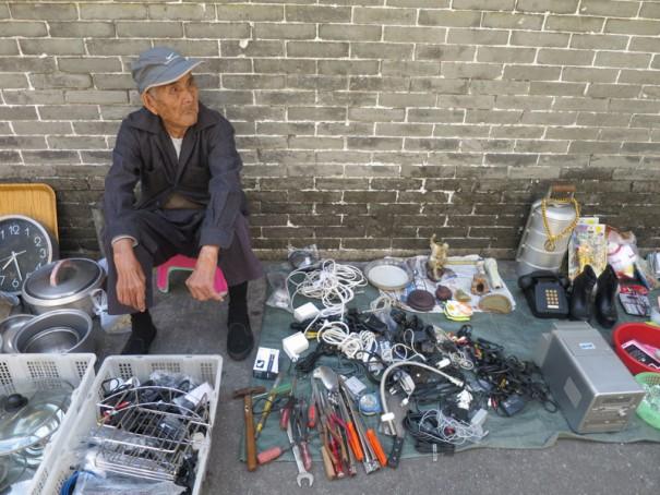 電話や靴、鍋の蓋などを路上に並べて売るおじいさん。