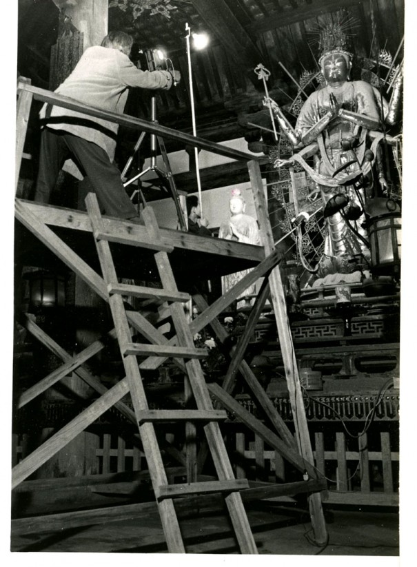楼を組んで不空羂索観音像を撮影する入江泰吉。仏像との真剣な対峙の姿勢が背中に溢れている。