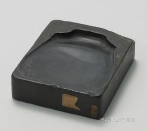 漱石遺愛の硯のひとつ「端渓双鳳硯」。こうした硯と筆と巻紙を用いて、漱石は門弟や友人に多くの手紙を書いた。硯縁の装飾図案は、背中合わせの鳳凰の図だという。写真/神奈川近代文学館蔵