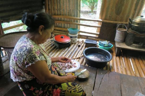 座って台所仕事をするモン族のおばあさん。たくさんの魚を塩漬けに。