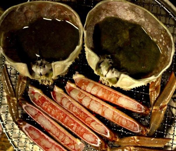 コンロの炭火で新鮮な間人カニを焼く。間人カニのみそはやや黒味がかった色をしている。