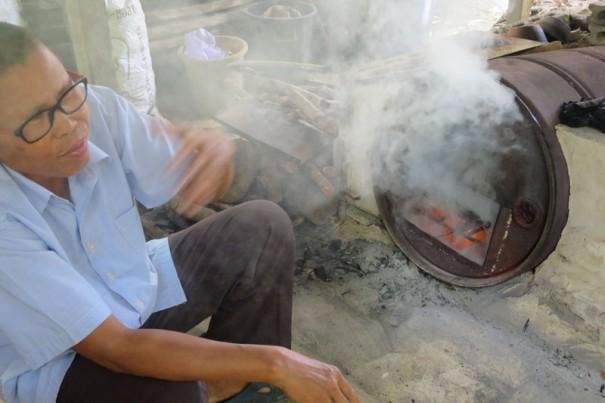 炭焼き場で。「煙がすごくて」と顔をしかめるスタッフ。