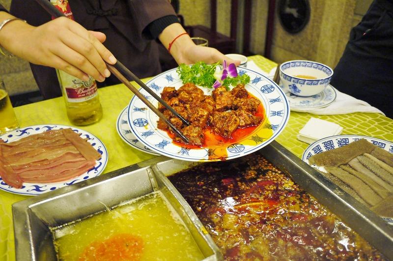 成都市の名店『龍森園』の火鍋。唐辛子や山椒で下味をつけた排骨(パイコー、骨付きの豚スペアリブ)を、煮えたぎる鍋に投入する。