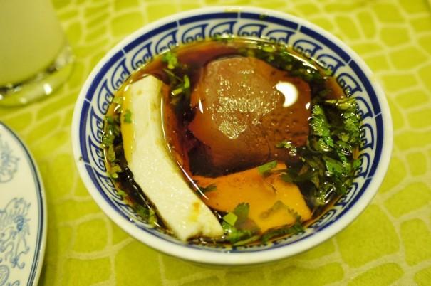 火鍋のタレは胡麻油。右の赤黒いレバーのような塊は、鴨の血をかためたもの。左の白い塊は豆腐。