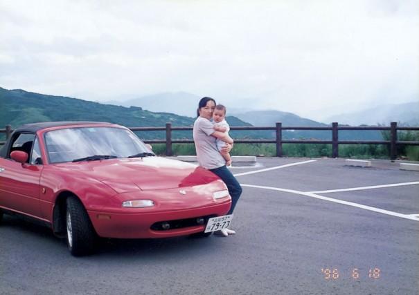 1996年に一亀さんが撮影した、生後4か月の長男・悠生君を抱いて愛車のロードスターに腰掛ける倫子さん。場所は高知 市内から車で約1時間のキャンプ場「ゆとりストパーク」。