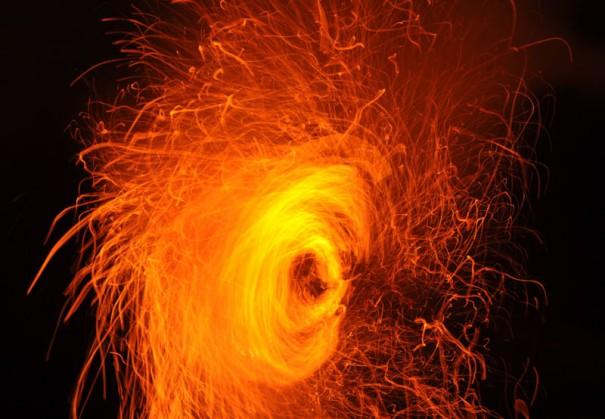 舞台の上でぐるぐる回される松明。火の粉や燃えかすが舞台下に飛び散る(撮影=牧野貞之)。