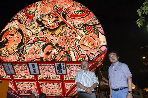 扇型のねぷたを前にする直木賞作家の安部龍太郎さん(左)と筆者。