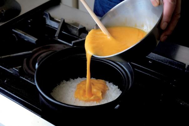 ④ 土鍋で炊いた熱々のご飯(米2合をといで土鍋に入れ、水430㏄を加えて1時間浸ける。蓋をして中火で10分、沸騰したら弱火で15分加熱し、火を止め15分蒸らす。)の上に、あらかじめ溶いておいた卵をまんべんなくかけ回す。