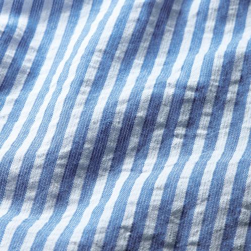強く張った撚糸と緩く張った撚糸を交互に織ることで凹凸が生まれる「シアサッカー」生地。通気性がよく蒸れを防ぐ。