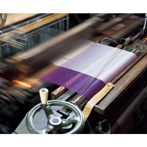 ストールのような薄ものの生地は繊細。人と機械とが一心同体の状態にならなければ、きれいには織り上がらない。
