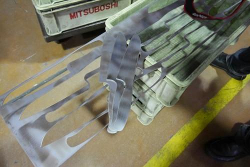 プレス機によって包丁の元型が打ち抜かれる。素材は幅約245×長さ1055㎜の細長い金属板だ。1枚から16本(牛刀の場合)型が取れる。隙間が生じないように効率よく打ち抜いていくのが腕の見せどころだ。このあと、1枚1枚歪みがないように精密にプレスされる。(長村金属株式会社)