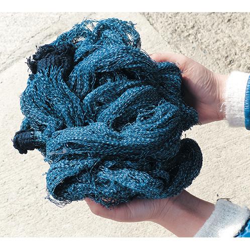 貴重な本藍で染まった残糸の束。廃棄するはずの材料で生地を作る発想が『TUGU』を生み出した。