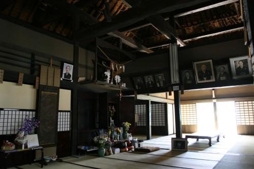 天井がなく、梁と屋根裏がよく見える。中央に見えるのは仏壇。梁に張られた名前の板は、行事などで親族が集まった際に座る位置を示したもの。