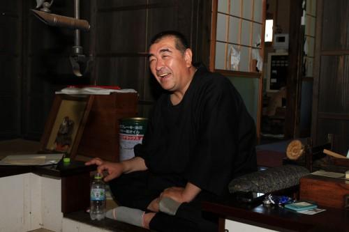 囲炉裏の前で家の歴史を語る、第46代当主・鈴木杢之助重廣さん。