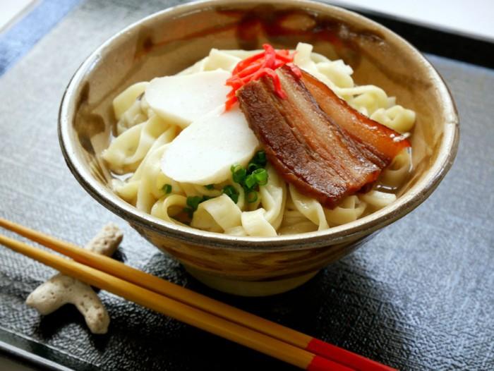 「沖縄そば」の上にのる具は豚三枚肉(バラ肉)の煮付けとかまぼこ、それに青ねぎと紅生姜が基本。三枚肉の代わりに、ソーキ(あばら肉)をのせると「ソーキそば」となる。