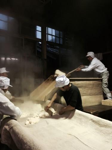 甑から蒸したばかりの酒米を掘り出す。