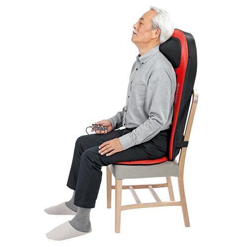 後ろをベルトで留めるだけ、ダイニングの椅子にも簡単に取り付けられる。持ち運んで、好きなところでマッサージが受けられる。