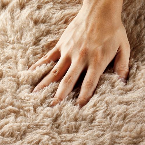 約32mmの長い毛足に手のひらが沈み込む。毛玉ができにくくなめらかな感触で体を暖かく包む。