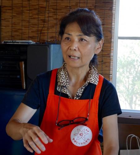 農園を訪れた人に、クワンソウについて説明をする座間味久美子さん。お茶をふるまいながら、「眠くなるので、運転する方はクワンソウのお茶は飲まないでくださいね」