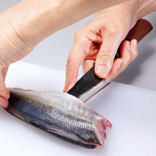 万能包丁の「三徳」は出刃としても使える。人差し指を刃の峰におき、その延長に刃先を持ってくる感覚で捌いていく。