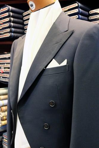 燕尾服に白麻のポケットチーフをスリーピークにして挿した例。