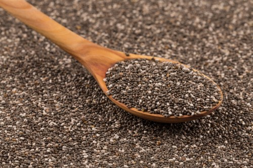 Chia seeds in a wooden spoon on chia background