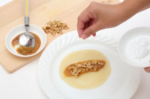 (4)焼き上がった皮に山椒味噌を塗り、クルミをのせ、砂糖をパラリと振って、くるりと包む。