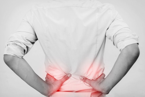 Young man in casual office shirt having hip pain