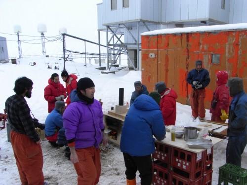 一次隊のプレハブ小屋の前でピザを楽しむ隊員たち