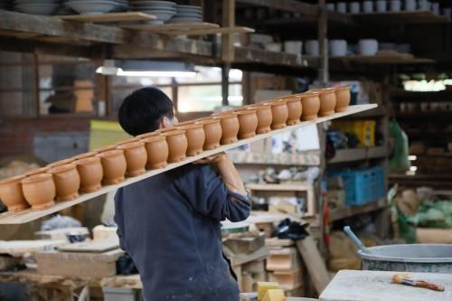 成形した器を運ぶ若き陶工。