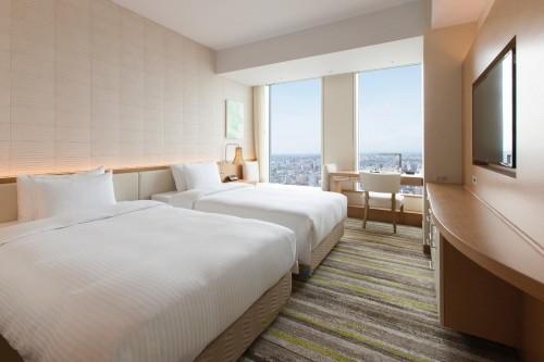 写真はスーペリアツイン。ゲストルームはすべて天井高が2.8mあり、窓も広いので開放感があります。東側の部屋は名古屋の繁華街、西側はJR線路、南側はオフィスビル、北側は一宮・岐阜方面の景色が望めます。