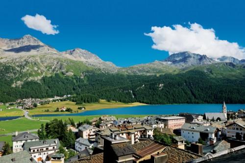 ENGADIN ST. MORITZ - Blick auf Silvaplana am Fusse des Julierpass am Silvaplanersee. Im Hintergrund der Dorfteil Surlej und der Piz Surlej (3188m), Munt Arlas (3127m) und der Piz Corvatsch (3451m). View of Silvaplana at the foot of the Julier Pass on the lake of Silvaplana. In the background: the village area of Surlej and the peaks of Piz Surlej (3188m), Munt Arlas (3127m), and Piz Corvatsch (3451m). Vista su Silvaplana ai piedi del Passo dello Julier presso il Lago di Silvaplana. Sullo sfondo la frazione di Surlej, il Piz Surlej (3188m), il Munt Arlas (3127m) e il Piz Corvatsch (3451m). Copyright by ENGADIN St. Moritz By-line:swiss-image.ch/Robert Boesch