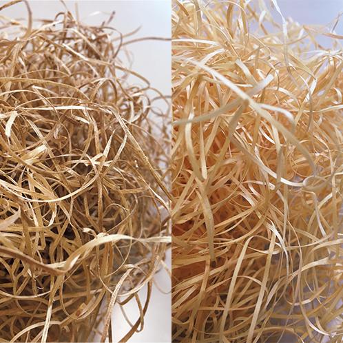 「もくめん」(木毛)と呼ばれる木材の緩衝材を作るメーカーが新たな商品開発に挑んだ。左は楠、右は檜のもくめん。それぞれのチップと合わせて充填されている。