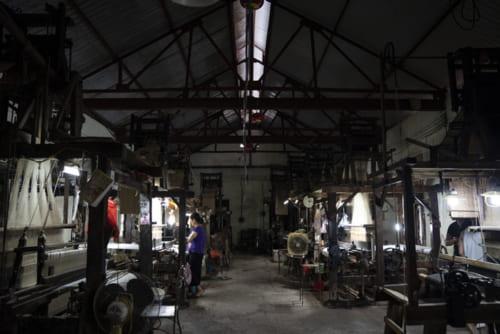 工房の中に入ると機織り機がずらりと並ぶ。
