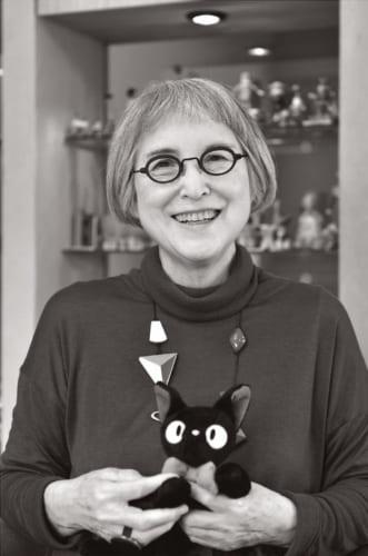 お洒落のポイントは眼鏡。その日の気分でかけかえる。手にしているのは『魔女の宅急便』の主人公キキの相棒、猫のジジのぬいぐるみ。
