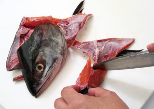 鮭の頭とカマの部分を庖丁で切り離す。さらに食べやすいように5㎝ほどの大きさに切り分けていく。