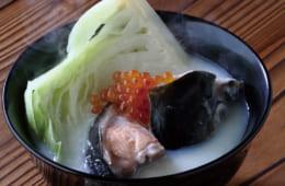 椀に鮭のアラとキャベツ、豆乳汁を盛り、仕上げにイクラをのせる。魚介と豆の蛋白質、野菜を同時に摂取できるため栄養価にも富む。