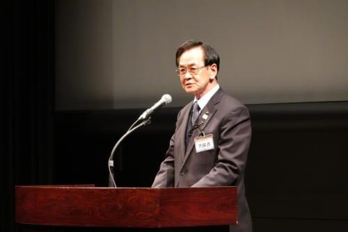 徳島県知事のメッセージを代読する徳島県政策監の福井廣祐氏
