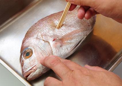 鯛の皮両面全体に、針打ちをする。金串や竹串がなければ楊枝を使ってもよい。縮みや破れを防ぐ。