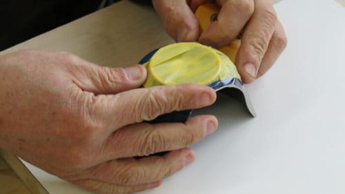 漆の付着を防ぐため、器の底にマスキングテープが貼られる