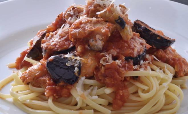 たっぷりの湯で茹でたパスタ麺の上に鍋のトマトソースを盛り付け、好みでパルミジャーノレッジャーノを振りかける。
