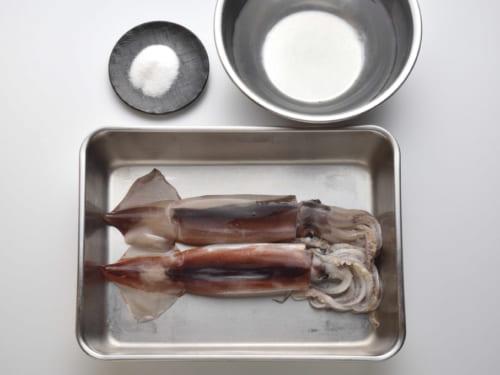 手前は新鮮なスルメイカ2杯、奥は下処理したイカを漬ける塩水の塩30gと水1L。