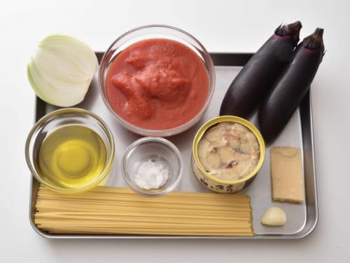 前列左はパスタ麺160g、右は大蒜ひとかけ。中列左からエクストラバージンオリーブオイル適量、塩少々、鯖の水煮缶(約200g)、パ ルミジャーノレッジャーノ適量。後列左から玉たま葱ねぎ1/2個、トマト水煮缶(約400g)、茄子2本。