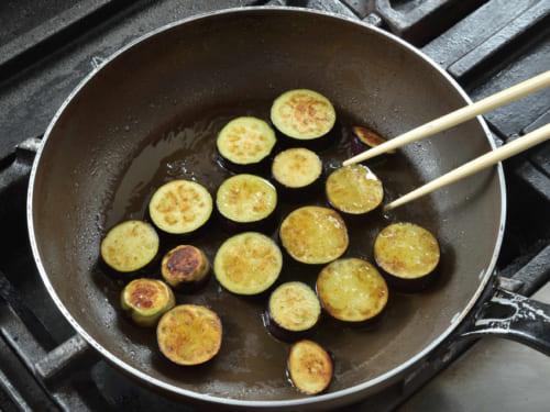 約1.5cm幅で輪切りにした茄子を、オリーブオイルで両面がきつね色になるまでしっかり炒める。