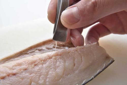塩鯖の半身には中骨が数本残っているので、指で骨を探りながら骨抜きで取り除く。