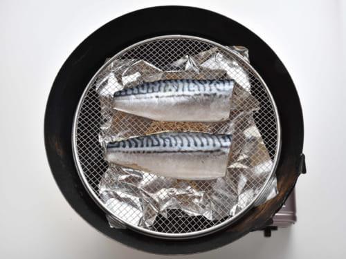 中華鍋に敷いたアルミ箔の上に桜チップを置き、網を載せて皮目を上に鯖を並べる。