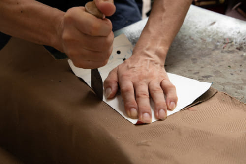 熟練の無駄のない動きで、型紙を当てて、ヘリンボーン生地をカットしていきます。