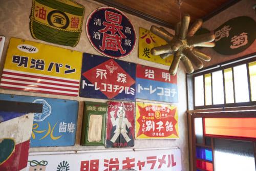 玄関にあるのは、ホーロー看板。鉄版に陶剤を焼き付けているので、風雨に強い。右から左に向かって書いてあるのが戦前のもの。右上の金色のオブジェは、明治時代にお菓子屋さんで飾られていた金平糖の看板を復刻したもの。